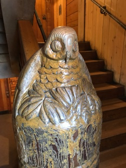 A discarded cedar utility pole, re-purposed in a stairwell at the lodge with an eagle carving.