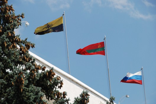 The Transnistrian flag (center) is the only flag in the world that continues to use the hammer and sickle logo. This flag flies over Bender city hall along with the Bender city flag (left) and Russian flag (right). The Russian flag is often flown alongside the Transnistrian flag as a sign of free association with the country.