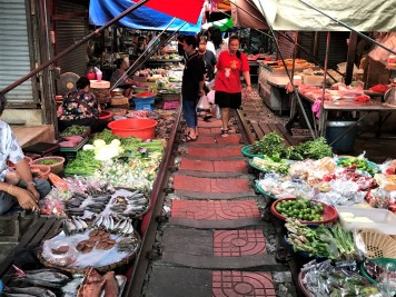 Shoppers walking the train tracks at Maeklong Railway Market