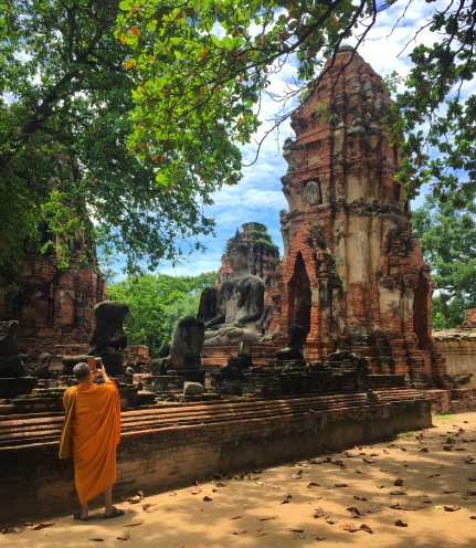 A Buddhist monk capturing the scene at Wat Mahathat