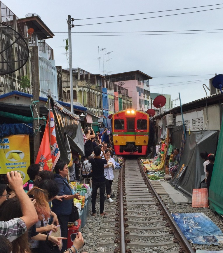 The train slowly creeps through the Maeklong Railway Market several times a day