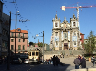 The tiled facade of Igreja Paroquial de Santo Ildefonso with one of the city's historic trams